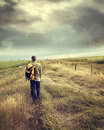 man-walking-down-country-road-29683842